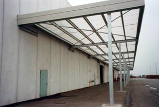 Pensilina con struttura in ferro a portale. La copertura è stata realizzata con pannelli in traslucido.