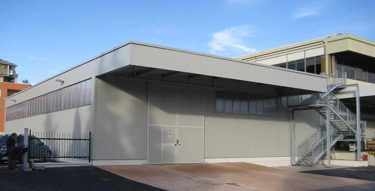 Salone industriale con struttura metallica in ferro e scala di sicurezza laterale.